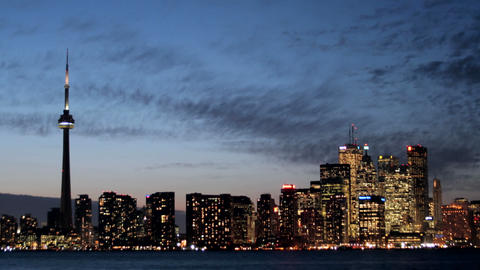 The lights of the Toronto skyline glow brighter under a colorful darkening sky Footage