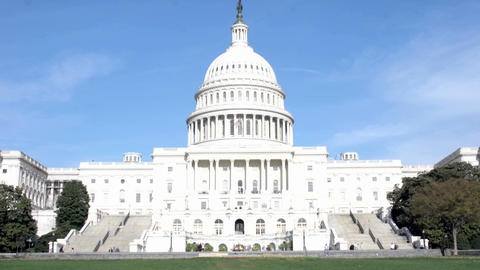 Workers and pedestrians enter, exit, and walk by the United States Capitol Building Footage