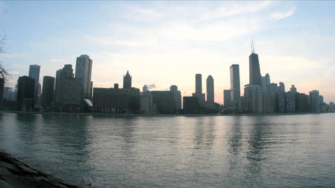Lake Michigan reflects the Chicago skyline as evening darkens into a colorful sky Footage