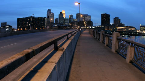 Pedestrians and vehicles cross a bridge in downtown Minneapolis as the evening sky darkens to night Footage