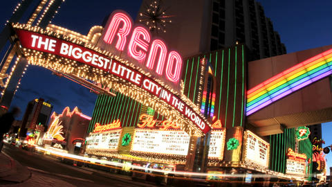 Tilt shot of accelerated traffic passing under a welcome sign for Reno, Nevada, the Biggest Little C Footage