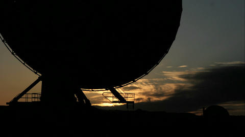 Time lapse shot of New Mexico's NRAO radio telescope's movement throughout the golden hour, and into Footage