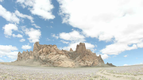 Sunlight reflects in patches as fluffy white clouds pass over New Mexico's Shiprock Footage