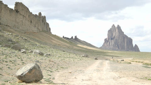 A dirt road leads to Shiprock monument Stock Video Footage