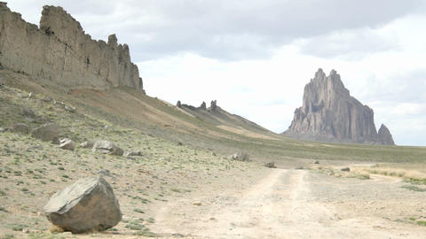 A dirt road leads to Shiprock monument Footage