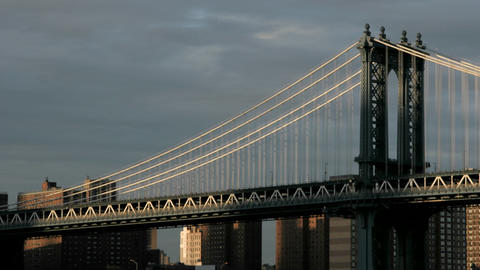 Accelerated traffic zips across the Brooklyn Bridge beneath a darkening cloudy sky Footage