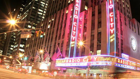 Slow, downward pan of an accelerated shot of traffic passing in front of Radio City Music Hall at ni Live Action