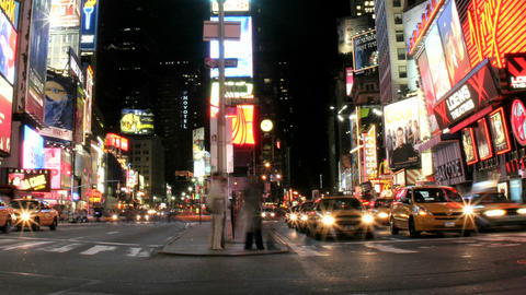 A slow left pan of an accelerated shot of traffic and pedestrians in New York's Times Square Footage