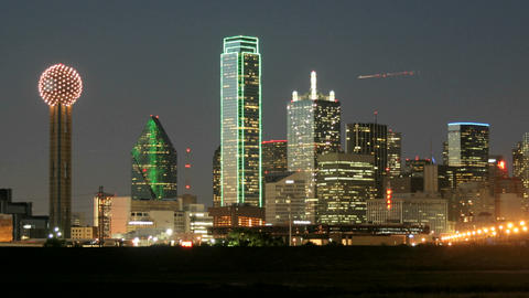 Slow pan of city lights illuminating the Dallas skyline at night Footage