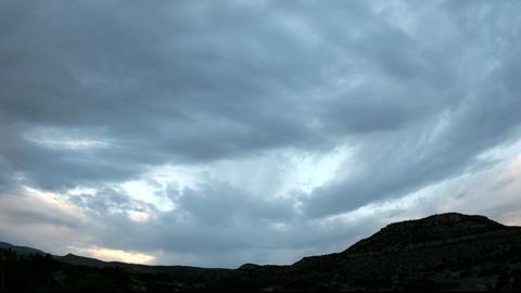 Golden light flares at the horizon beneath dark storm clouds Stock Video Footage