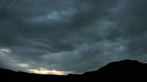 Golden light flares at the horizon beneath dark storm clouds Live Action