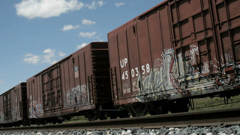 Time lapse shot of fluffy white clouds passing over old railroad boxcars Footage