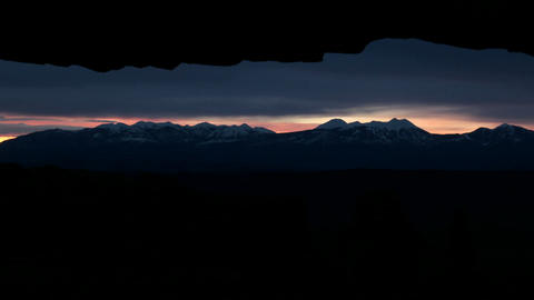 Clouds of darkness lighten into delicate shades of pink as the sun rises over Mesa Arch in Canyonlan Footage