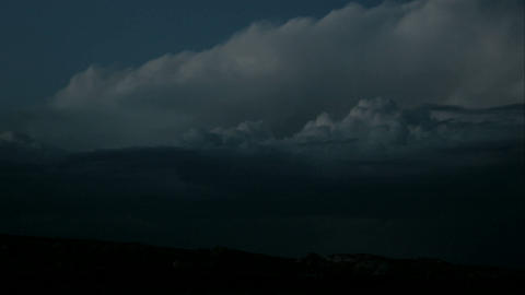 Lightning flashes from swiftly moving storm clouds over... Stock Video Footage