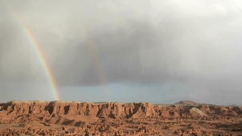 A rainbow fades in the sunlight as it arches over Goblin Valley State Park Footage