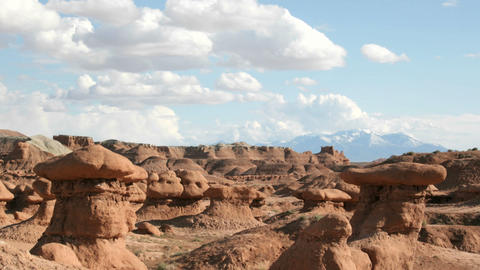 White clouds float in a blue sky over Goblin Valley State... Stock Video Footage