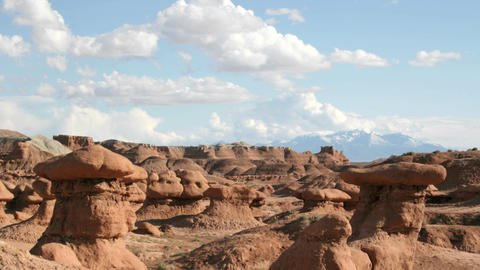 White clouds float in a blue sky over Goblin Valley State Park Footage