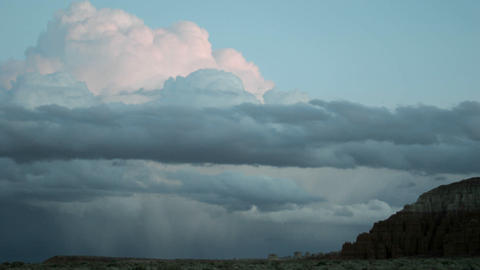 Thunderheads over Goblin Valley State Park take on shades of pink in the golden-hour Footage
