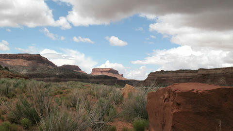 Slow right-pan of a time-lapse shot showing clouds passing over Utah's Mexican Hat Canyon Footage