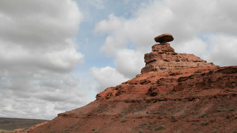 Storm clouds pass over a small rock tower in Mexican Hat... Stock Video Footage