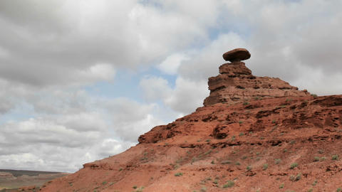 Storm clouds pass over a small rock tower in Mexican Hat Canyon Footage