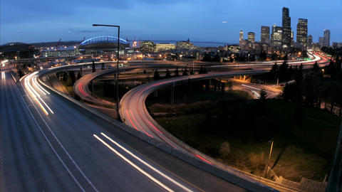 As the golden-hour darkens into night, accelerated traffic on the Seattle freeway blurs into streaks Footage