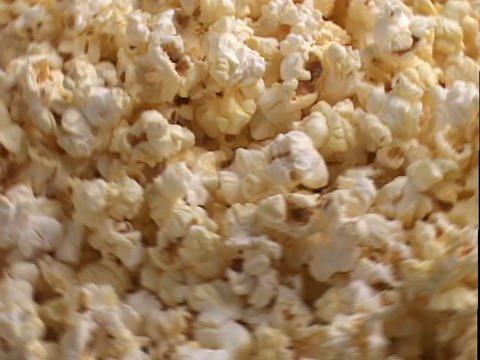 Buttered popcorn is shined on by spotlights in a display Stock Video Footage