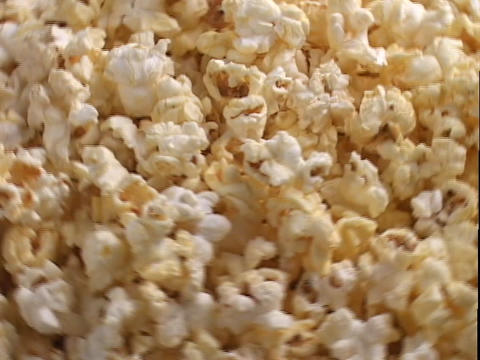 Buttered popcorn is shined on by spotlights in a display Footage