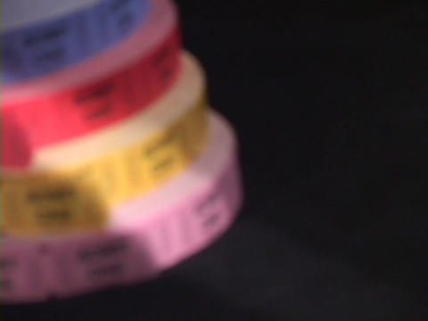 Pan-left to four large rolls of colorful tickets Footage