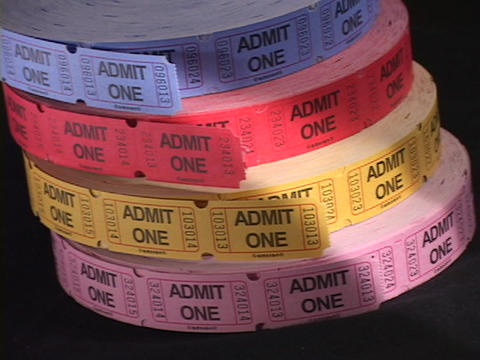 Pan-left to four large rolls of colorful tickets Stock Video Footage