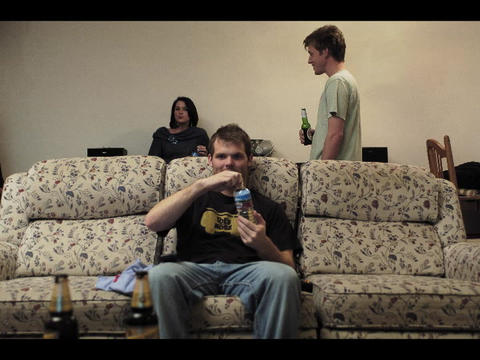 A college student sits on a sofa and drinks a soda as... Stock Video Footage