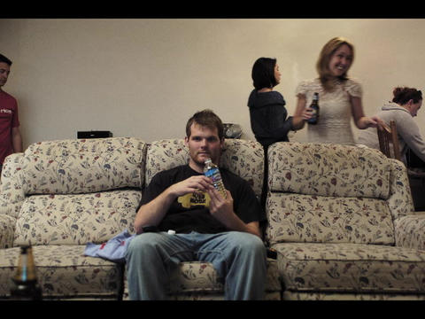 A college student sits on a sofa and drinks a soda as people come and go around him Footage