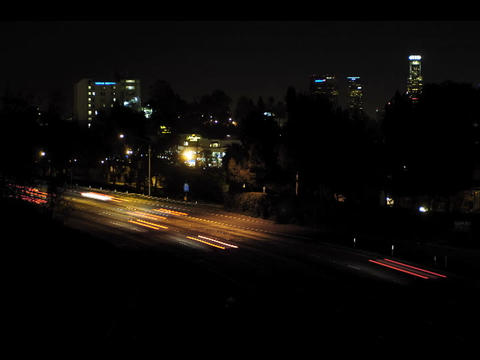 An accelerated view of traffic flowing at night with a view of skyscrapers in the background Footage
