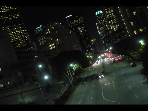 An accelerated aerial view of city traffic at night with skyscrapers in the background Footage