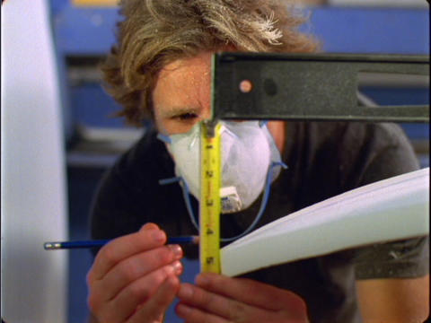 A man wearing a dust-mask carefully measures an object... Stock Video Footage