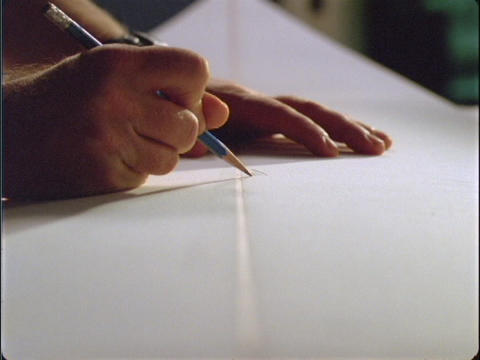 A close-up of a person's hands writing on a white board Live Action