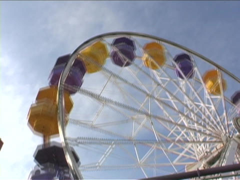 A ferries wheel with yellow and blue carriages spins at a... Stock Video Footage