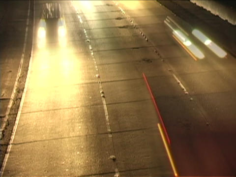 Heavy traffic speeds along a dark highway Footage