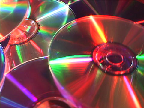 Colored lights reflect off revolving compact discs Stock Video Footage