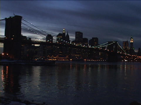 A city bridge and skyline glow at golden-hour Stock Video Footage
