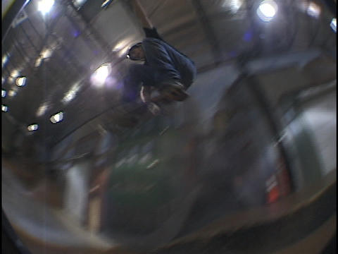 A skate-boarder makes a jump at an indoor skate park Stock Video Footage