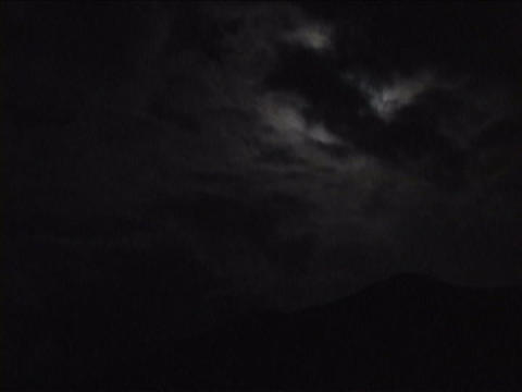 Clouds move past the moon Stock Video Footage