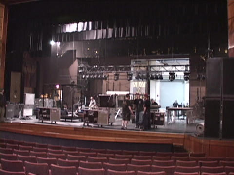 A stage crew tears down props and lighting equipment Live Action