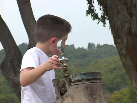 A little boy drinks from an outdoor drink fountain Stock Video Footage