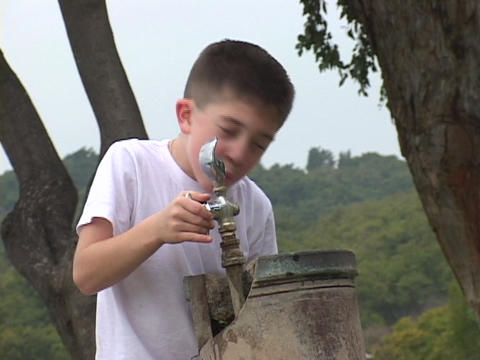 A little boy drinks from an outdoor drink fountain Live Action