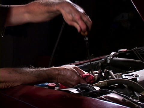 A mechanic checks the oil dipstick Stock Video Footage
