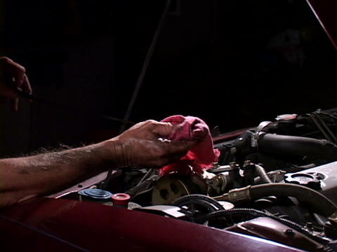 A mechanic checks the oil dipstick Footage