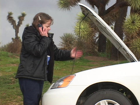 A woman talks on her cell-phone as she looks under the hood of her smoking car Footage