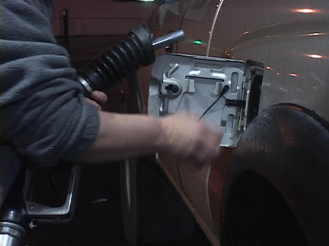 A hand squeezes a gas nozzle to fill up a car Footage