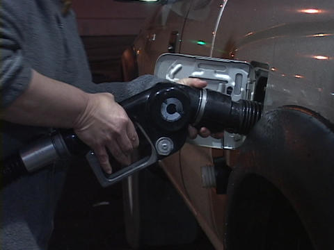 A hand squeezes a gas nozzle to fill up a car Stock Video Footage